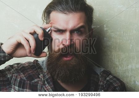 Surprised Bearded Man Applying Perfume On Face With Open Mouth