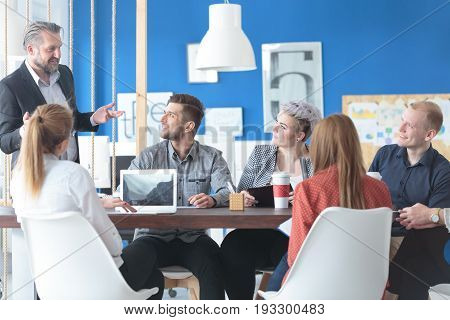 Team of young employees eagerly listening to their manager's speech