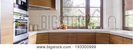 Wooden cupboards and white worktops in classic kitchen