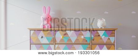 Cute colorful commode in little baby's room. On the shelf pink bunny and glass pig
