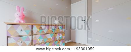 Little children's bedroom wth pink wallpaper and colorful commode with toys on it