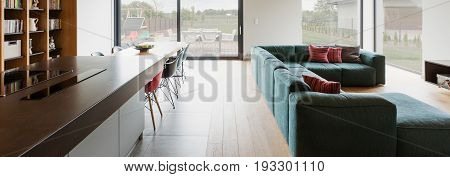 Spacious living room connected with wooden floor connected with dining hall and kitchen. In the background big windows with view outside