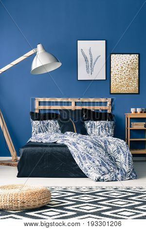 Bed with wooden bedhead on blue wall