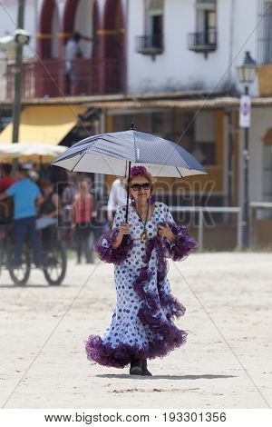El Rocio Spain - June 2 2017: Female pilgrim in a traditional flamenco dress in El Rocio during the pilgrimage Romeria 2017. Province of Huelva Andalusia Spain