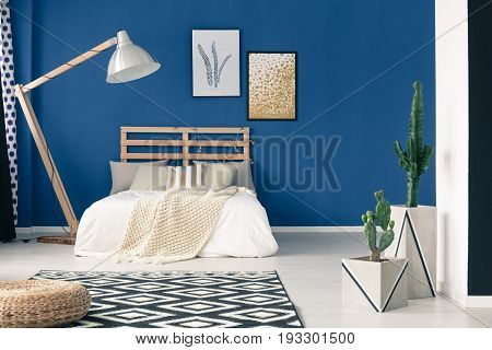 Stylish gold and white bedclothes in blue bedroom