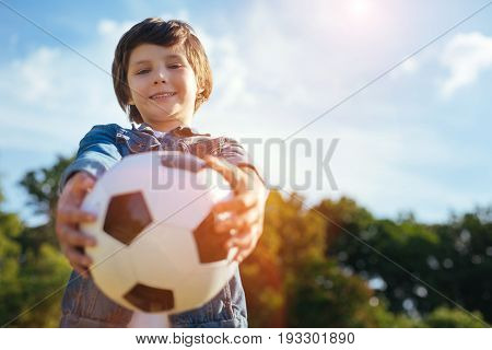Lets play. Ambitious easy going talented child handing a ball and asking playing with him while spending an active weekend outdoors
