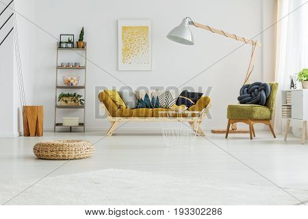 Mustard couch with colorful pillows standing under oversize lamp