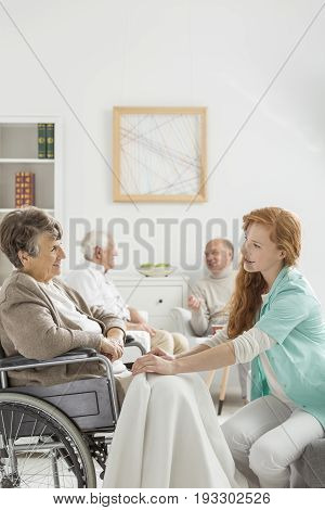Young nurse covering senior lady in wheelchair with a blanket