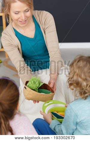 Teacher holding plush vegetables in basket during classes with kids