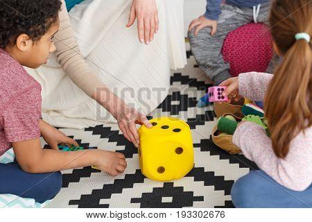 Big yellow plush dice on a carpet in kindergarten