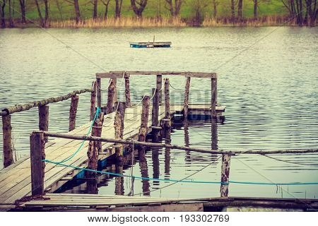 Nature concept. Oldfashioned old wooden jetty on lake shore during autumnal weather.