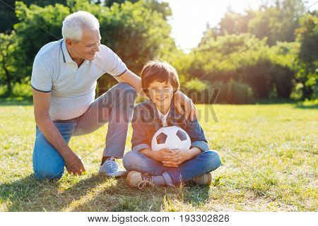 Great hobby. Vibrant energetic intelligent man taking his grandkid in the park and encouraging his passion for sports by paying football with him