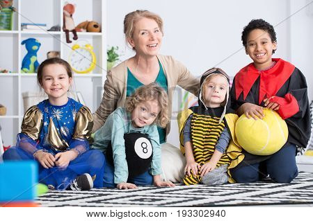 Dressed up children in colorful costumes and happy kindergarten teacher