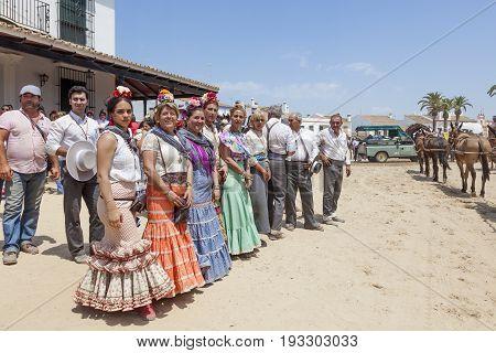El Rocio Spain - June 2 2017: Group of pilgrims in traditional flamenco dresses in El Rocio during the pilgrimage Romeria 2017. Province of Huelva Andalusia Spain