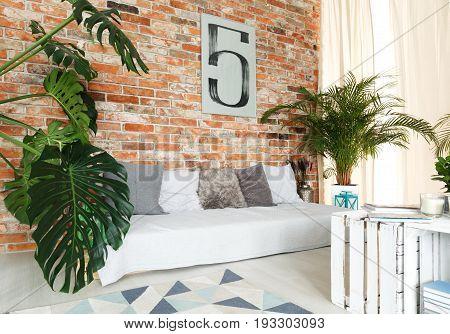 Stylish DIY white sofa next to raw brick wall