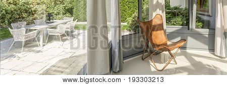 Glazed bay windows in orangery with a leather butterfly chair and view on the garden with furniture