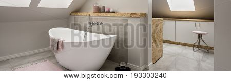 Bathroom in the attic with an oval bathtub and moving on to the utility room with cupboards