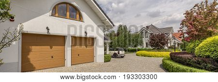 View of the driveway to the double garage in large detached house with well-kept garden