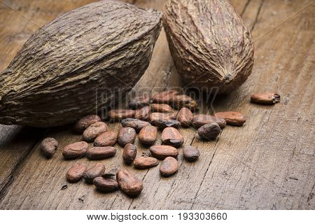 cocoa pods with cocoa beans on wooden table
