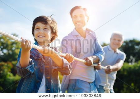 Real support. Enthusiastic focused nice family acting as a team while playing tug war and having fun outdoors in the park