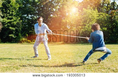 I will win. Fun hilarious sincere child trying his strength against dad and pulling the rope while playing with him outdoors