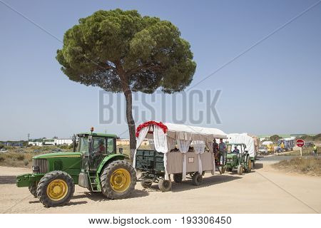 El Rocio Spain - June 2 2017: Pilgrims with tractor trailers on the road to El Rocio during the pilgrimage Romeria 2017. Province of Huelva Andalusia Spain