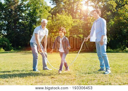 Creative use. Witty wonderful handsome family members having an active weekend in the park and playing with his family while having a lot of fun