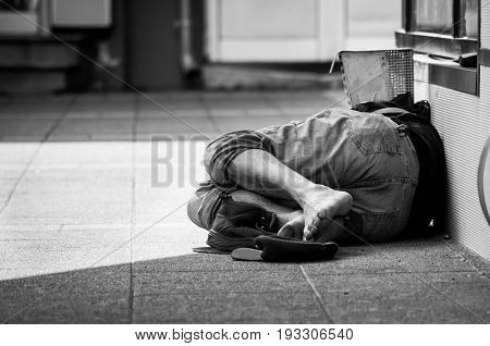 Homeless man sleeps on the street, in the shadow of the building. Social documentary street.