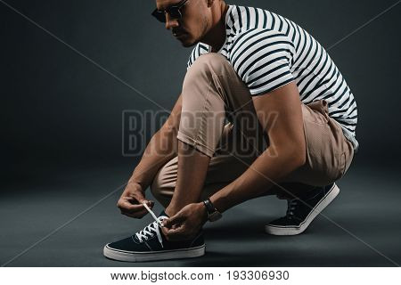 Handsome Stylish Middle Aged Man In Striped T-shirt And Sunglasses Tying Shoelaces In Studio