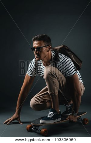 Handsome Stylish Man In Sunglasses Crouching On Skateboard And Looking Away