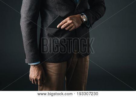 Cropped Shot Of Stylish Man Putting Smartphone In Pocket Of Blazer