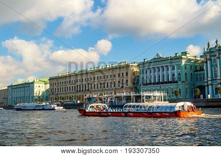ST PETERSBURG RUSSIA - OCTOBER 3 2016. The Great Old and Small Hermitage buildings on the Palace embankment of Neva river and touristic sailboat floating on the water area in St Petersburg Russia.St Petersburg Russia landmarks