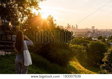 LONDON, UK - MAY 22, 2017: Woman standing on the top of the hill at Greenwich Park during sunset and taking photos on smartphone. Every year millions of Londoners and tourists visit Greenwich Park.