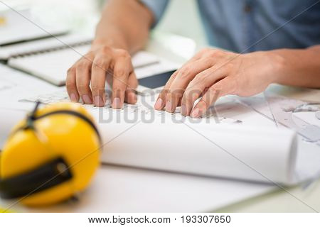 Hands of engineer working with the tool on project drawings background at construction site