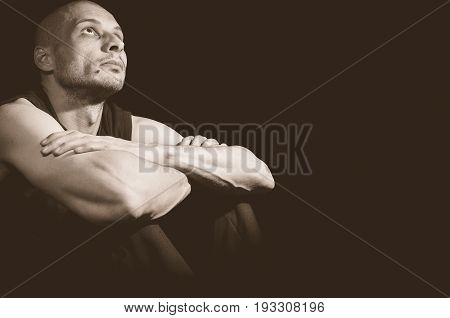 Depressed man looking up and searching for God. Dark image. Dark background. Loneliness. Depression. Sadness.