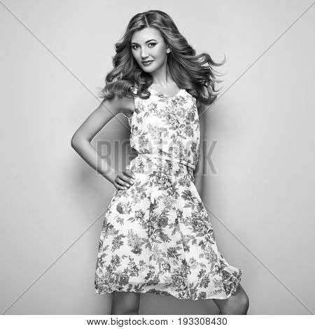 Blonde young woman in floral summer dress. Girl posing on white background. Stylish wavy hairstyle. Fashion Black and White photo. Blonde lady