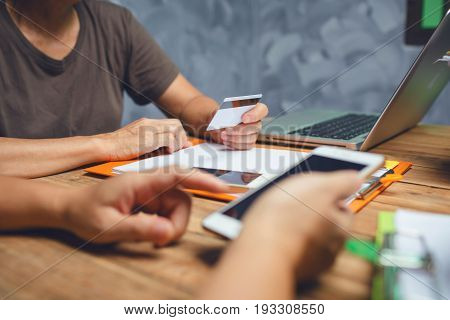 Female Business Holding A Credit Card For Online Shopping By Mobile Apps While Working In The Office