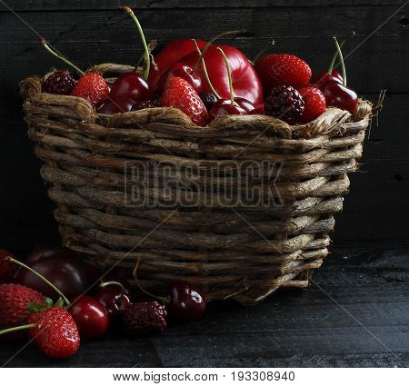 Red fruits in liana basket. Black wood background.