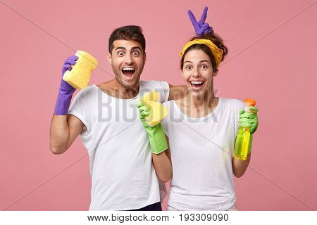 Young Male And Female Playing Fools While Standing Against White Pink Wall Resting After Doing Clean