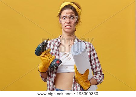 Portrait Of Confused Female With Dirty Face Wearing White Top With Shirt, Protective Eyewear And Glo