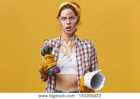 Shocked Woman In Protective Gloves, Checkered Shirt And Yellow Headband Holding Drill And Rolled Pap