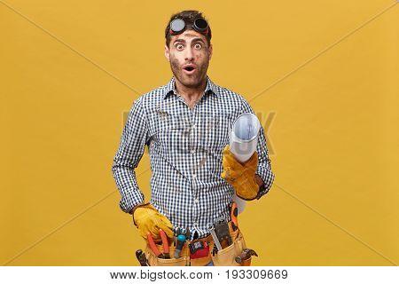 Studio Portrait Of Shocked Handyman Wearing Checkered Shirt, Protective Eyewear And Gloves, Tool Bel