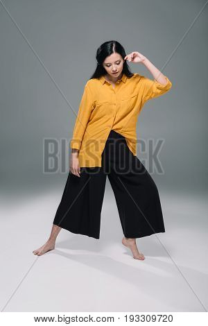 Elegant Attractive Model Posing In Yellow Blouse And Black Wide Trousers, Isolated On Grey
