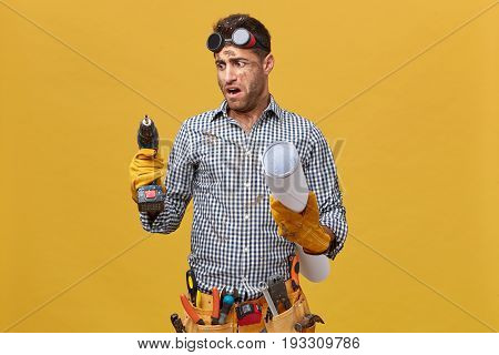 Portrait Of Dirty Repairman Having Tool Belt Holding Blueprint And Drill Machine Looking At It With