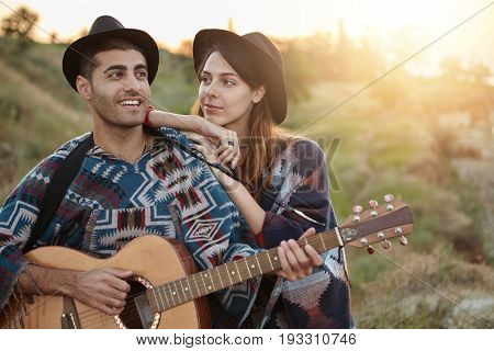 Lovely Romantic Couple Sitting Outdoors Singing Songs And Playing Guitar. Pretty Female Wearing Blac