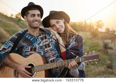 People, Romance, Relaxation, Lifestyle Concept. Couple In Love Sitting On Meadow Admiring Sunrise Pl