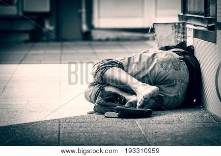 Homeless man sleeps on the street, in the shadow of the building. Social documentary.