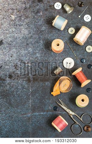 Various sewing accessories and tools for needlework. Old scissors, wooden coils with threads, needles, thimbles, measuring tape and buttons on a blue background.  Top view.