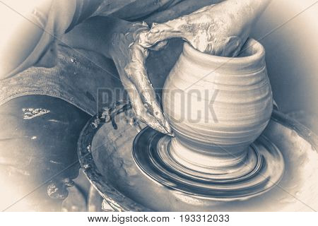 Photo in old vintage style. Girl sculpts in clay pot closeup.