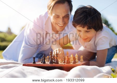 Nice move. Logical brilliant lively kid learning the rules of the intellectual charade while his dad teaching him playing chess